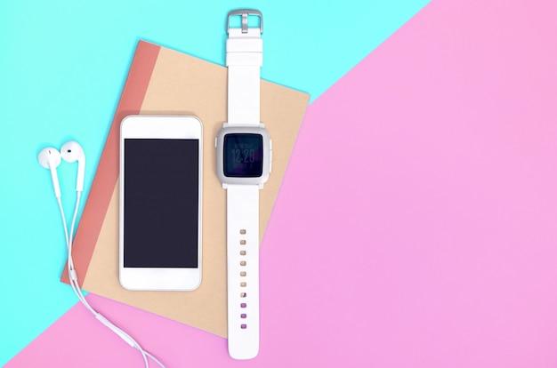 Téléphone portable vide avec des gadgets de smartwatch sur rose bleu