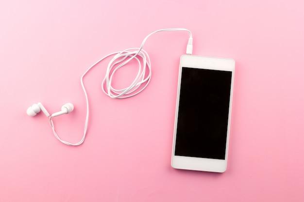 Téléphone portable vue de dessus avec fond rose casque