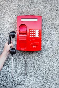 Téléphone public de rue rouge sur le mur et une main d'homme ramassant le téléphone