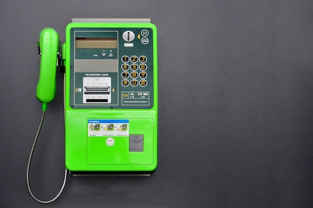 Téléphone public vert sur fond de couleur noire