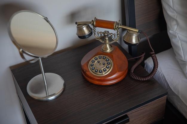 Téléphone rétro se dresse sur une table en bois dans une chambre d'hôtel