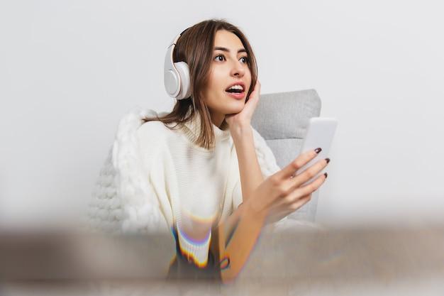 Téléphones portables. portrait de la belle femme brune à manches longues douces et confortables isolées sur fond de studio blanc. confort à la maison, émotions, expression faciale, concept d'ambiance hivernale. espace de copie.