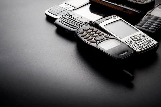 Téléphones portables vieux et obsolètes sur fond noir.