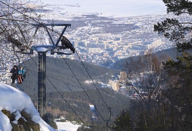 Télésiège avec des gens qui vont à la montagne tserkovka vue de dessus de la station balnéaire de belokurikha