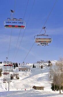 Télésiège sous ciel bleu et au dessus de la piste de ski