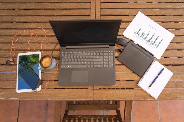 Télétravail à domicile depuis le jardin avec ordinateur portable et autres gadgets. vue aérienne.