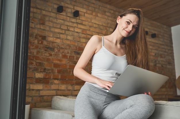Télétravailleur blonde séduisante souriante avec un ordinateur assis sur le bord du canapé