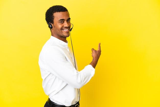 Télévendeur afro-américain travaillant avec un casque sur fond jaune isolé pointant vers l'arrière