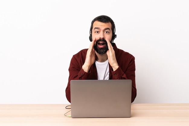 Télévendeur caucasien homme travaillant avec un casque et avec un ordinateur portable criant et annonçant quelque chose