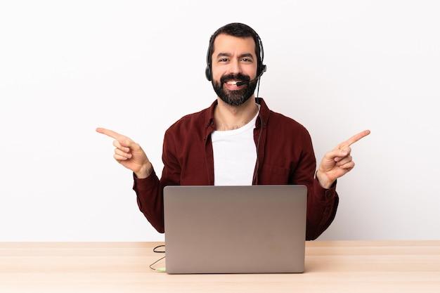 Télévendeur caucasien homme travaillant avec un casque et avec un ordinateur portable pointant le doigt vers les côtés et heureux