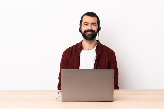 Télévendeur caucasien homme travaillant avec un casque et avec un ordinateur portable en riant