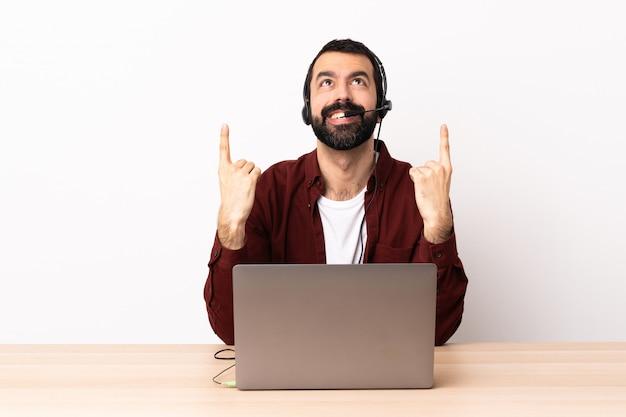 Télévendeur caucasien homme travaillant avec un casque et avec un ordinateur portable surpris et pointant vers le haut