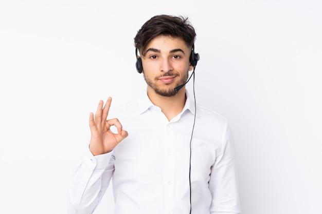 Télévendeur homme arabe travaillant avec un casque isolé sur mur blanc montrant un signe ok avec les doigts
