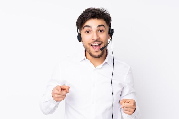 Télévendeur homme arabe travaillant avec un casque sur le mur blanc pointe le doigt vers vous