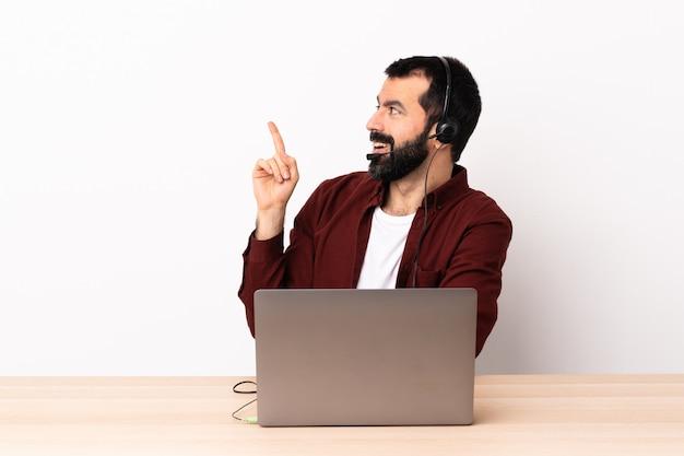 Télévendeur homme caucasien travaillant avec un casque et avec un ordinateur portable ayant l'intention de réaliser la solution tout en levant un doigt