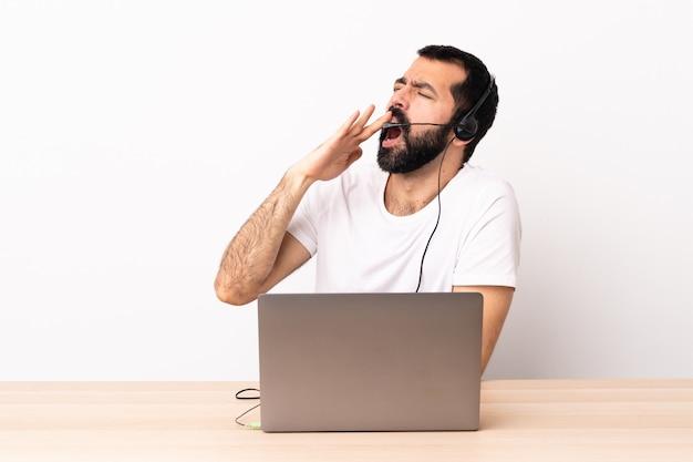 Télévendeur homme caucasien travaillant avec un casque et avec un ordinateur portable bâillant et couvrant la bouche grande ouverte avec la main