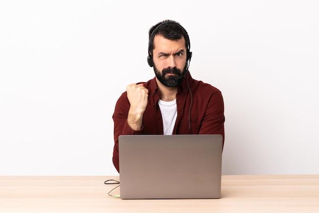 Télévendeur homme caucasien travaillant avec un casque et avec un ordinateur portable avec une expression malheureuse