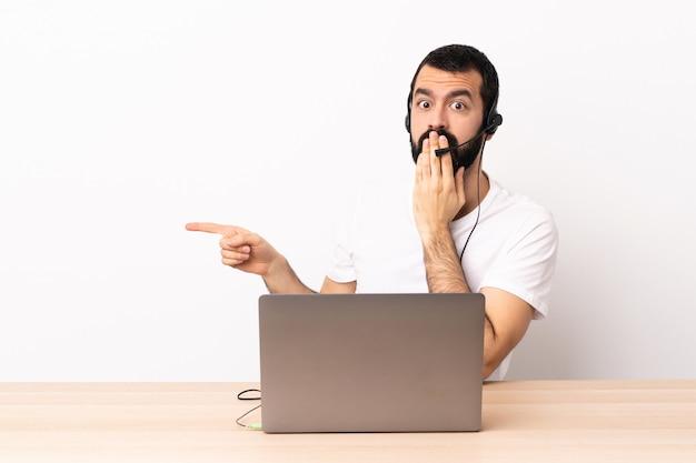 Télévendeur homme caucasien travaillant avec un casque et avec un ordinateur portable avec une expression surprise tout en pointant le côté