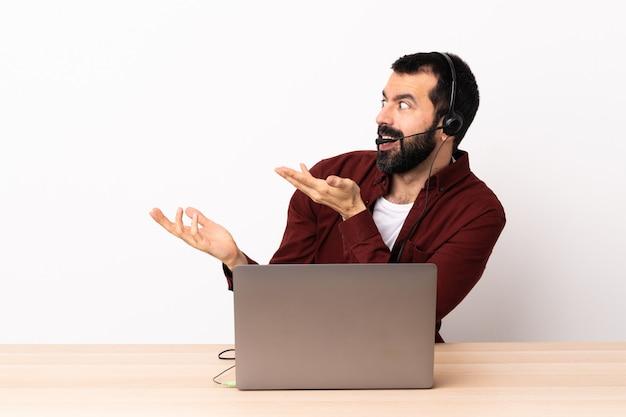 Télévendeur homme caucasien travaillant avec un casque et avec un ordinateur portable avec une expression surprise tout en regardant de côté