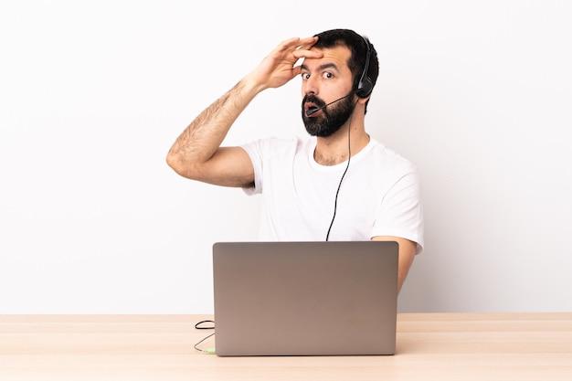 Télévendeur homme caucasien travaillant avec un casque et avec un ordinateur portable faisant un geste surprise tout en regardant sur le côté