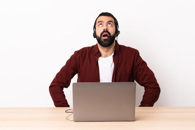 Télévendeur homme caucasien travaillant avec un casque et avec un ordinateur portable en levant et avec une expression surprise