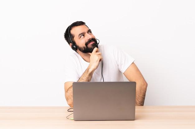 Télévendeur homme caucasien travaillant avec un casque et avec un ordinateur portable et levant