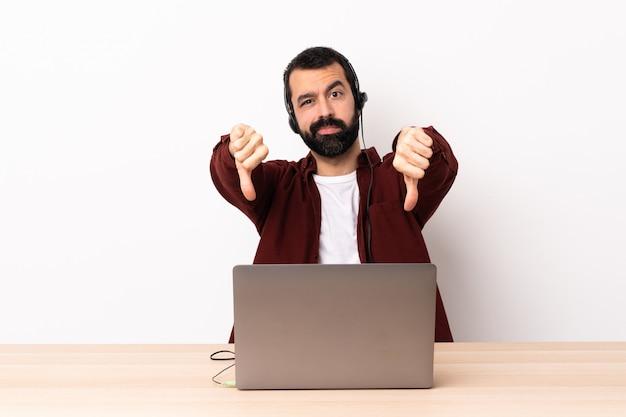Télévendeur homme caucasien travaillant avec un casque et avec un ordinateur portable montrant le pouce vers le bas avec deux mains