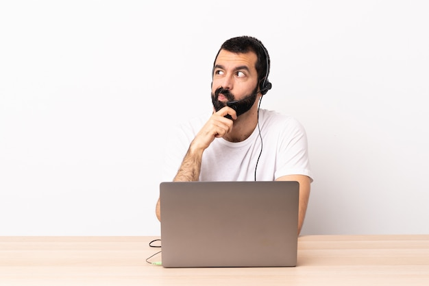 Télévendeur homme caucasien travaillant avec un casque et avec un ordinateur portable en pensant à une idée tout en levant