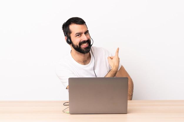 Télévendeur homme caucasien travaillant avec un casque et avec un ordinateur portable pointant vers l'arrière