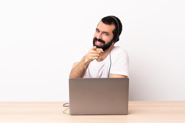 Télévendeur homme caucasien travaillant avec un casque et avec un ordinateur portable pointant vers l'avant avec une expression heureuse