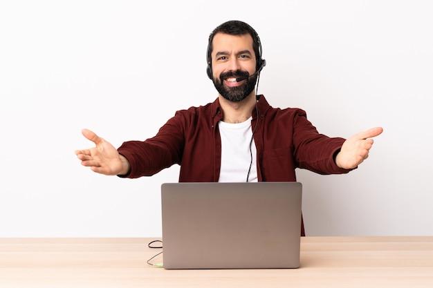 Télévendeur homme caucasien travaillant avec un casque et avec un ordinateur portable présentant et invitant à venir avec la main