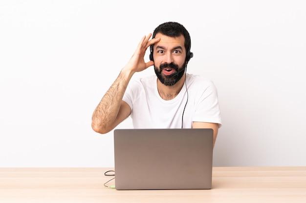 Télévendeur homme caucasien travaillant avec un casque et avec un ordinateur portable a réalisé quelque chose et a l'intention de la solution