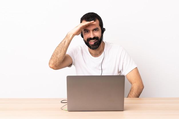 Télévendeur homme caucasien travaillant avec un casque et avec un ordinateur portable à la recherche de loin avec la main pour regarder quelque chose