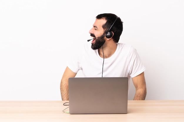 Télévendeur homme caucasien travaillant avec un casque et avec un ordinateur portable en riant en position latérale