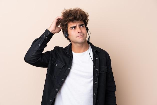 Télévendeur homme travaillant avec un casque ayant des doutes et avec une expression de visage confuse