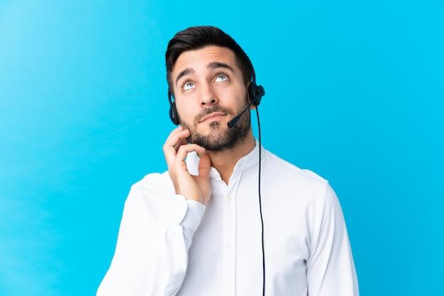 Télévendeur homme travaillant avec un casque sur bleu en pensant à une idée