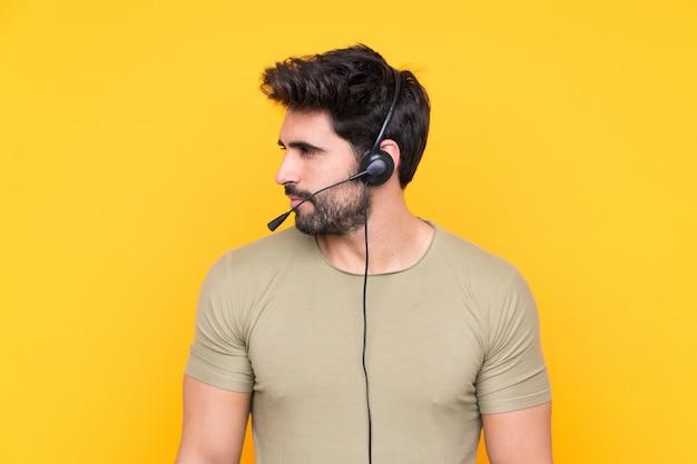Télévendeur homme travaillant avec un casque sur le côté jaune isolé mur à la recherche