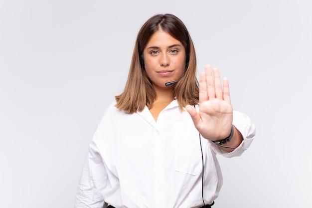 Télévendeur de jeune femme à la recherche grave, sévère, mécontent et en colère montrant la paume ouverte faisant le geste d'arrêt