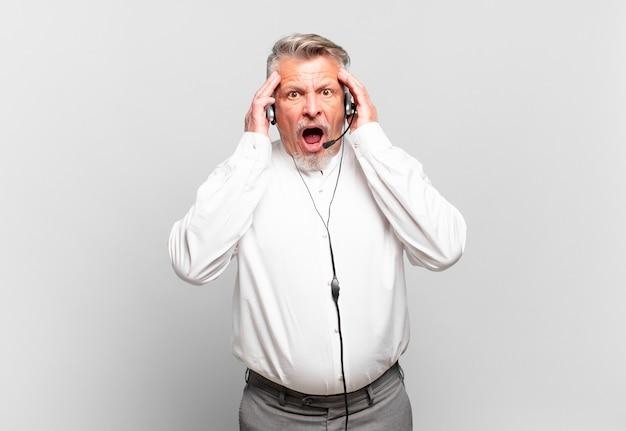 Télévendeur senior se sentant heureux, excité et surpris, regardant de côté avec les deux mains sur le visage