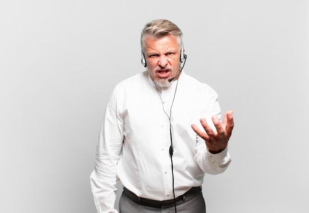 Télévendeur senior semblant en colère, agacé et frustré de crier wtf ou ce qui ne va pas avec vous