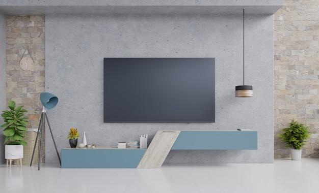 Téléviseur sur meuble bleu dans le salon moderne avec lampe, fleur et plante sur un mur de ciment.