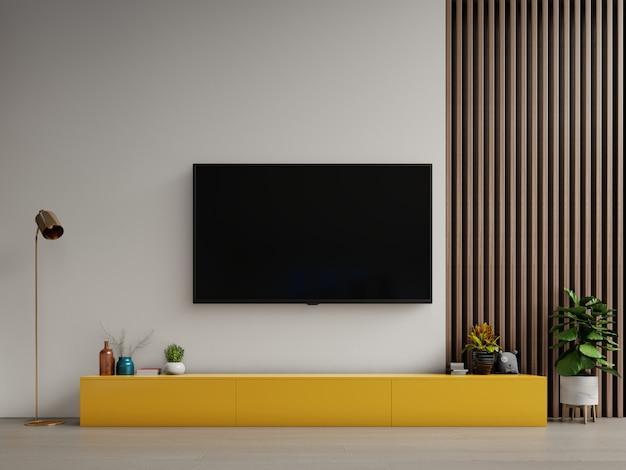 Téléviseur sur meuble jaune ou objet de salon dans un salon moderne avec lampe, table, fleur et plante sur fond de mur blanc.