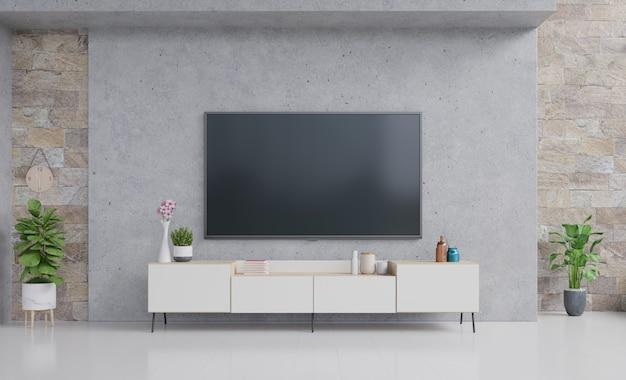 Téléviseur sur meuble de salon moderne avec lampe, table, fleur et plante sur un mur de ciment.