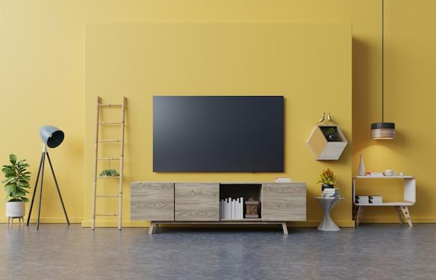 Téléviseur sur meuble de salon moderne avec lampe, table, fleur et plante sur un mur jaune.