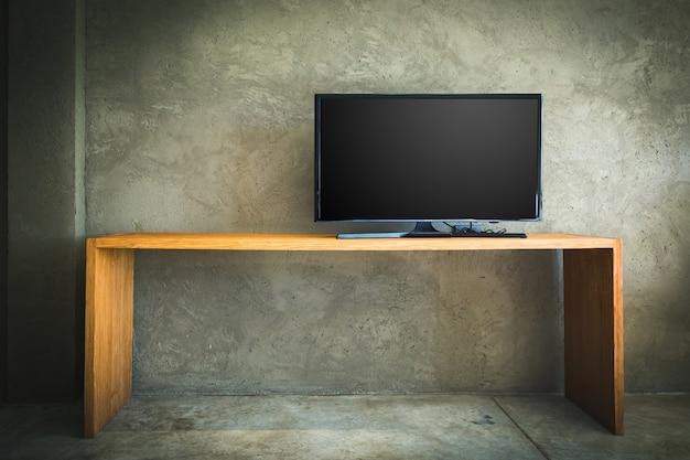 Télévision à écran plat lcd sur une table en bois dans le salon avec mur de béton grunge et parquet