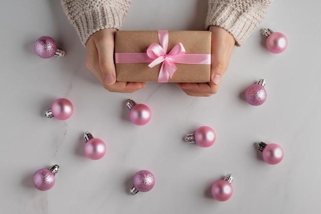 Télévision de noël poser avec enfant tenant une boîte-cadeau et des boules roses sur fond de marbre