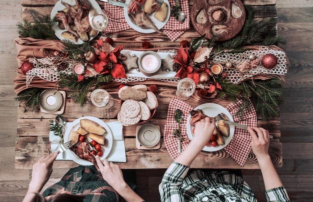Télévision à plat d'amis mains manger et boire ensemble. vue de dessus des personnes ayant fête, rassemblement, célébration ensemble à table rustique en bois