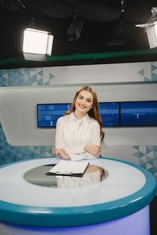 Télévision présente au studio se préparant pour une nouvelle diffusion. jeune fille souriante en chemise blanche assise à table.
