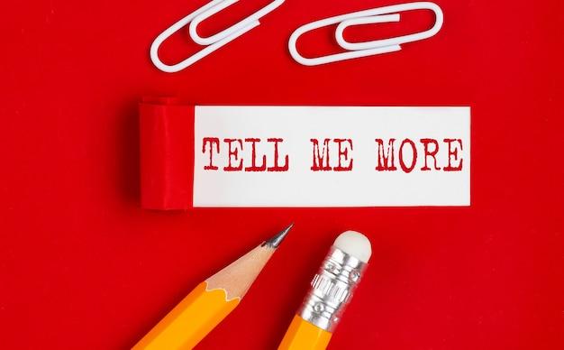Tell me more message écrit sous papier rouge déchiré avec des crayons et des clips