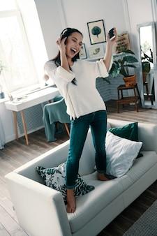 Tellement amusant! toute la longueur d'une jeune femme séduisante portant des écouteurs et souriant tout en dansant sur un canapé à la maison